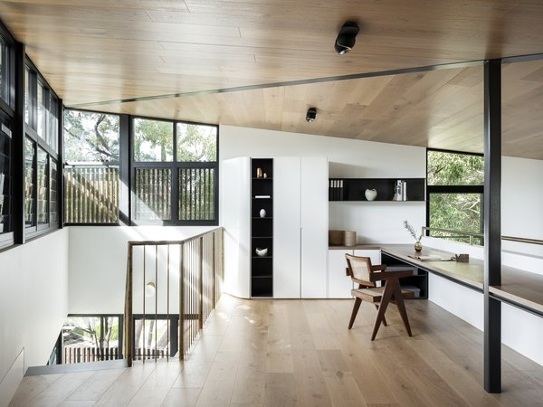 Above the kitchen, the mezzanine level holds a workspace with a view. The sharp pitch of the roof opens up the space below it, so this area doesn't feel cramped. Note the reoccurring motif of rounded joinery in the main spaces, which plays off of the angular moments.