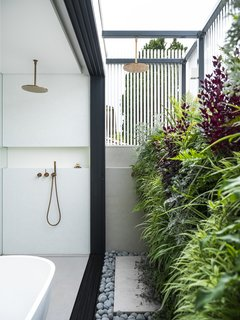 """The screening and this outdoor area off the en suite allowed them a garden at roof level—the green wall was the clients' idea!"" says Litera. ""It creates a beautiful buffer between the real world and their sanctuary."""