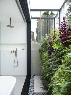 """""""隔墙和套房外的户外区域让他们在屋顶上有一个花园——绿色墙是客户的想法!""""""""文学说。""""它在现实世界和他们的避难所之间创造了一个美丽的缓冲区。"""""""