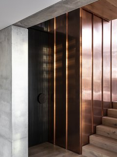 Just inside the entry, the material palette meets: concrete, copper, and oak.