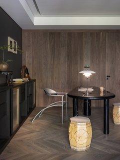 """在光的办公室,陈设计了一个上漆台加入Philippe Starck设计的椅子,路易·波尔森台灯,和中国民间""""鼓凳。"""""""