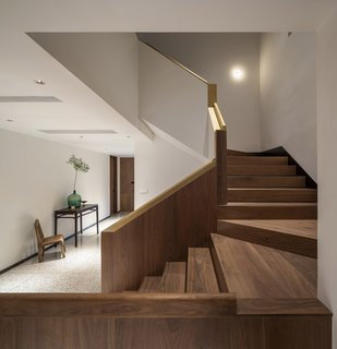 The wood staircase is capped with a smooth brass handrail.