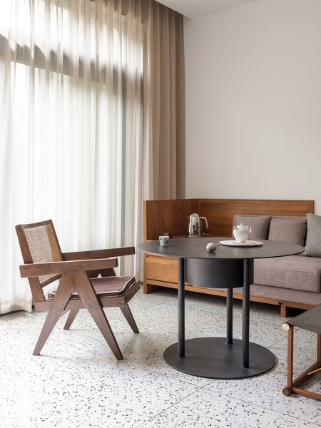 A vintage Pierre Jeanneret chair found by Guang sits beside a coffee table designed by Bob Chen. In the background, the tea station integrated with the couch has an outlet for an electric kettle and storage for supplies.
