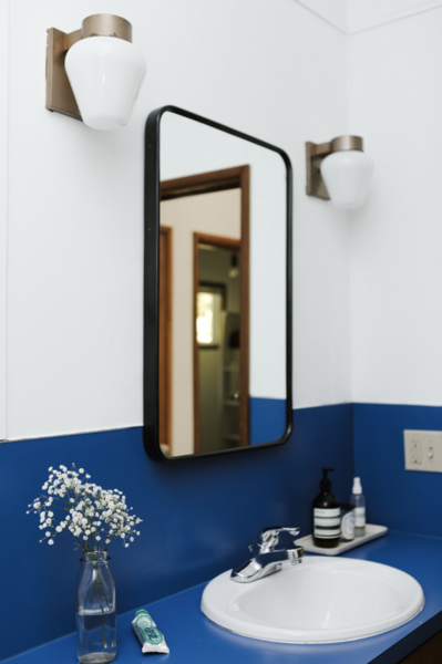 Crisp white paint modernizes the preserved cobalt blue counter. The mirror is from Rejuvenation.