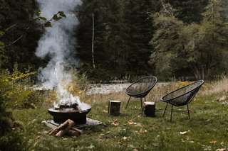 The river is just a few steps away. CB2 chairs sit with the firepit.