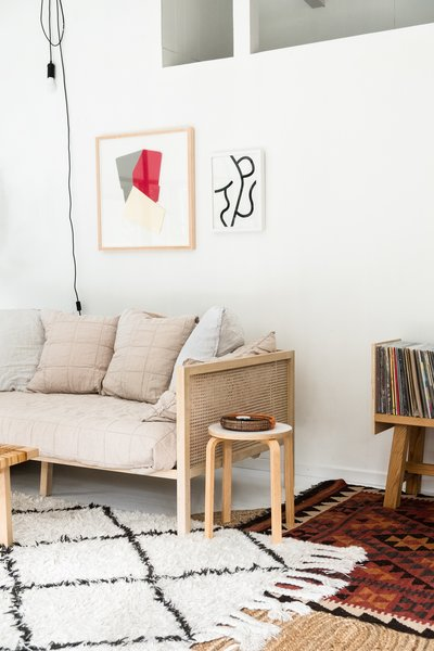 The Boho Natural Daybed by CB2 is piled with Parachute pillows and creates a cozy nest in the living room. The wall sconce is from France & Son.