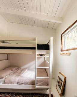 White paint makes the room feel bigger, and a bunk bed with a double-sized mattress on the bottom, utilizes the space more comfortably.