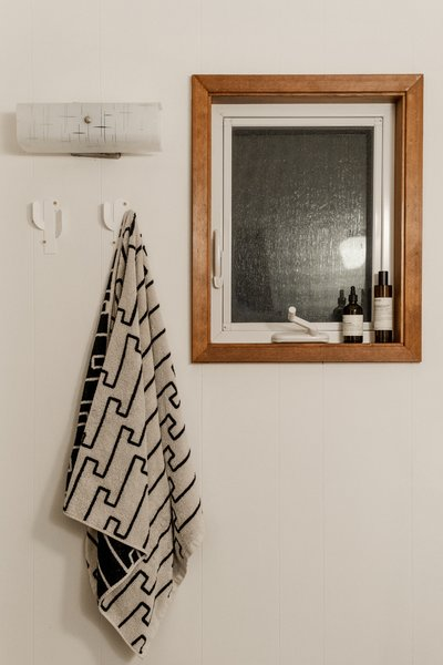A towel from Dusen Dusen hangs from wall hooks from Thing Industries.