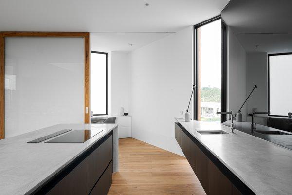 在厨房尽头的一扇滑动玻璃门后面,隐藏着一处办公空间。