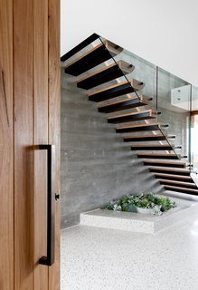 In the entry, an inset planter in the polished concrete floors sits beneath the open-tread staircase.