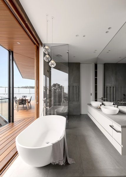 The bathtub gets pride of place. Large-format porcelain tiles at the floor and in the shower sync with the concrete counter on the floating vanity.