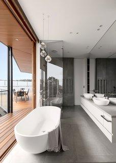 浴缸是最显眼的地方。地板和淋浴间的大型瓷砖与浮动梳妆台上的混凝土台面同步。