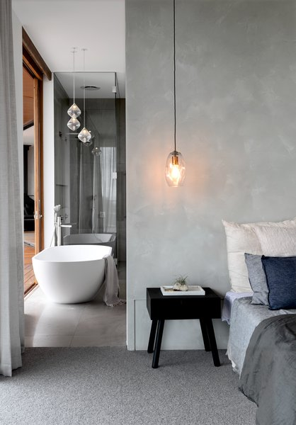 The grayscale tones of the bedroom extend into the adjacent bathroom to create a cohesive backdrop.