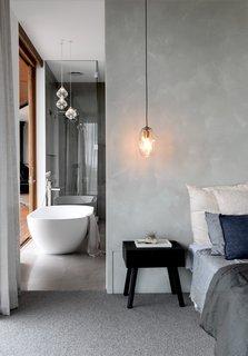 卧室的灰度调延伸到邻近的浴室,创造了一个连贯的背景。