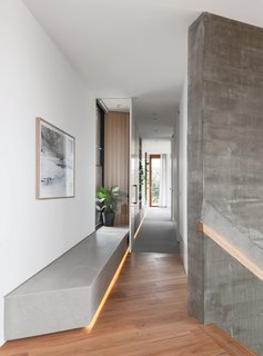 A change in flooring, from the blackbutt to soft carpeting, marks the transition from the living spaces to the principal suite. The corridor is lined with storage.