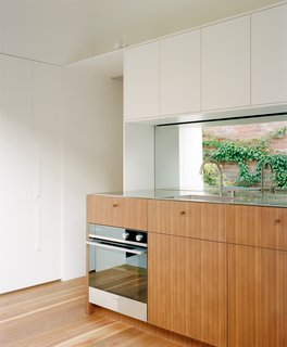 A mirrored backsplash reflects the garden. Spotted Gum cabinetry meets floors of the same material for uninterrupted flow. The counters are stainless steel.