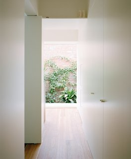 The corridor hosts the refrigerator and laundry units behind sleek white cabinetry fronts.