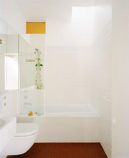 """在浴室里,新旧以意想不到的方式融合在一起。地板覆盖着传统的红色六角形地砖,""""这经常用于维多利亚时代的公共建筑,""""Bokey-Grant说。琥珀面板是一块传统的图案玻璃。Bokey-Grant说:""""我们原本打算重新使用在拆除过程中被拆除的窗户上的一块玻璃,但在拆除过程中它被打碎了,所以我们重新找了一块。""""""""这是对澳大利亚传统住宅中流行的原始扇灯/高光窗的改造。"""""""