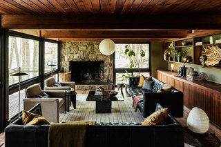 Black leather West Elm sofas anchor the room atop a gridded Annie Selke rug.