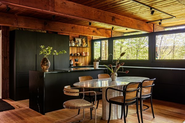 Rich black soapstone counters wrap black-matte IKEA cabinets, and appliances are hidden behind cabinet fronts so the room recedes. Storage now extends under the windows and lines the dining area, where the table and chairs were both Craigslist finds.