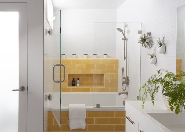 "Bright yellow tile now surrounds the tub picked out by the owners at the beginning of the remodel process. They wanted this room to feel ""like a spa or a happy place to retreat to,"" says Reeves."