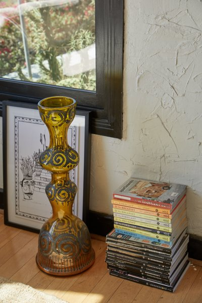 A vintage Murano glass vase sits with a framed etched print from artist Don Corleon.