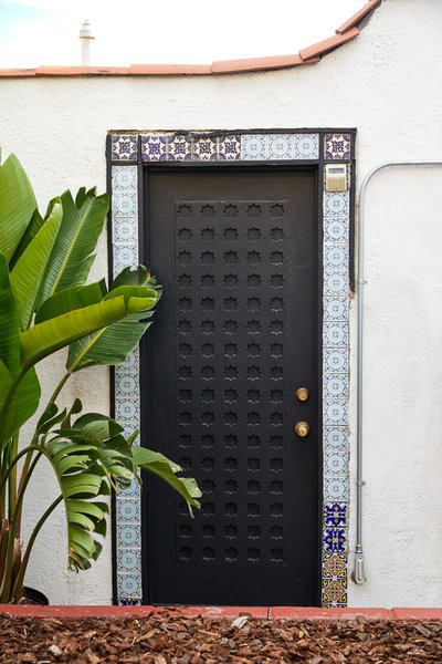 A 100-year-old door was painted in the Dark Arts color from Backdrop, to make the historic tile surround pop.