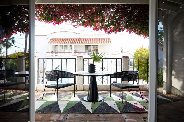 The downstairs patio is framed in bougainvillea and has two Boomerang Lounge rattan chairs with a mosaic-topped table, both from CB2.