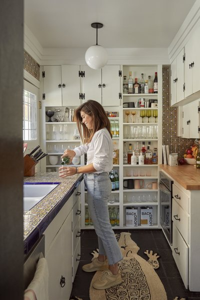 The quirky tiled kitchen holds much of its original charm and is Natalie's favorite room. The rug is the Schumacher Charlap Hyman & Herrero Caiman Alligator rug from Chairish.