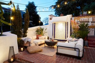 The living room sports original tiling, the Bizerte sofas from CB2, LED string lights from Costco, and a fresh coat of Backdrop's 'Supermoon' exterior paint.