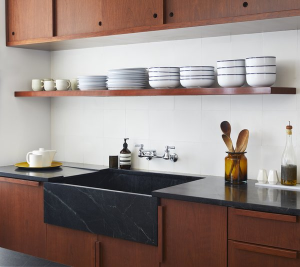 A soapstone apron-front sink with an integrated drainboard adds a simple yet luxe touch. The single floating shelf puts everyday dishes close by without creating visual clutter.