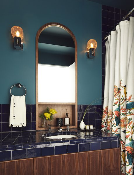 """It's kind of a moody, dark bathroom,"" says Tang. An inset walnut mirror custom-designed by Tang mingles with zellige tiles by Mosaic House. The vanity sconces are theater wall lights from Germany by Cosack, sourced via 1stdibs."