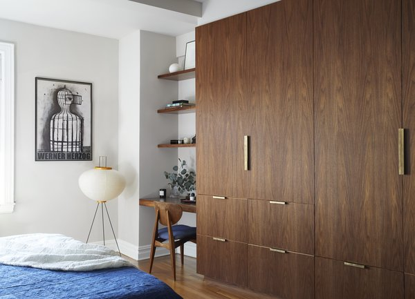 The bespoke walnut storage and brass hardware in the principal bedroom was designed by Tang. The lamp is by Noguchi.