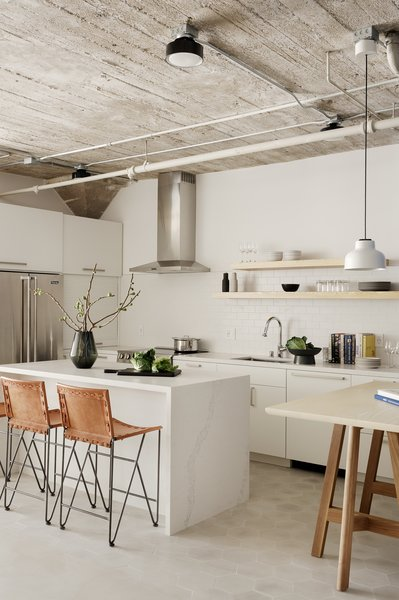Honed Caesarstone Calacatta Nuvo wraps the new island and tops the white cabinets. A wall of tall storage now occupies the former eating area—including an appliance garage with a roll-up door for hiding clutter.