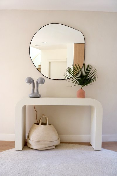 After the remodel, the streamlined palette throughout begins in the entry, where a Horseshoe Ivory Lacquered Linen Console Table from CB2 partners with a table lamp from Entler, mirror from Zara Home, and rug from Nordic Knots.