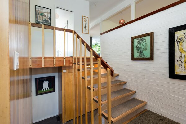 The front door opens to the landing of a floating staircase.