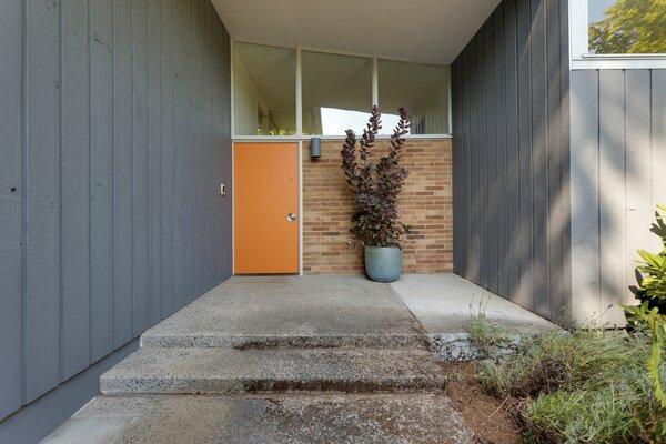 Punchy orange paint dresses the front door.