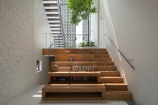 The stepped wooden platforms provide built-in seats for the library. Down the stairs to the left is a guest room.