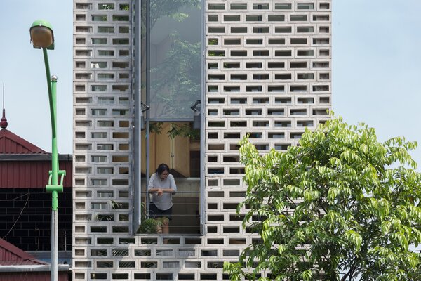 A window breaks up the street-facing facade composed of perforated cement blocks.
