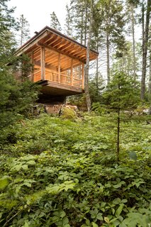 Sited on a rock ledge, the Far Cabin's screened porch cantilevers over the forest floor for a tree house effect.