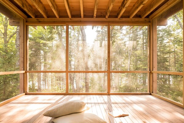 "The screened porch ""added even more flexibility to how [the clients] would be spending time there,"" says Shaw, and immerses them in the forest setting with providing protection from the bugs, including Maine's notorious black flies."