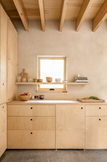 """Streamlined birch plywood cabinetry and a maple butcher-block counter forms the kitchenette, which isn't intended for extensive meal prep. The building is a blend of """"a bedroom and camping,"""" says Shaw, which means much of the cooking and cleaning happens outside."""