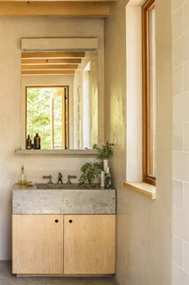 In the bathroom, a concrete sink basin and shelf cast by a local artisan sits over a birch vanity.