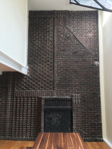 """Before: The two fireplaces bring a lot of character to the apartment. """"They're both working fireplaces with this super interesting, almost Victorian-patterned brickwork that we thought was really unique and we wanted to keep as a defining feature in those spaces,"""" says Greenwald."""