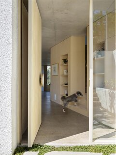 The front door pivots open. The interior floors are polished concrete.