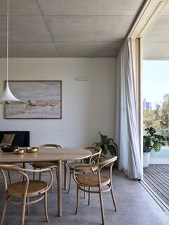 Thonet chairs surround a table from Made by Morgen, and the pendant is by Cult Design. The dining room cedes to an exterior terrace.