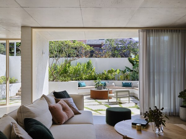 "The living room opens to the private, walled exterior courtyard at the front. ""I really love the design of the courtyard and the fact that you can see it from everywhere in the house,"" notes Fox. The ottoman is from Jardan and the outdoor chair is Hay."