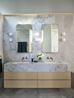 """Astra Walker faucets bedeck the vanity. The aged brass and honed marble """"further reflect the human interaction with nature and time,"""" says Fox."""