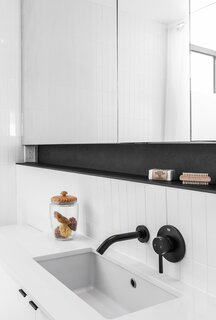 An integrated shelf underscores a large mirror, which makes the room feel larger.