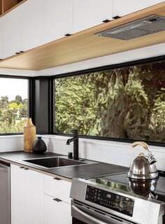 A ribbon window lines the counter and looks into the trees.